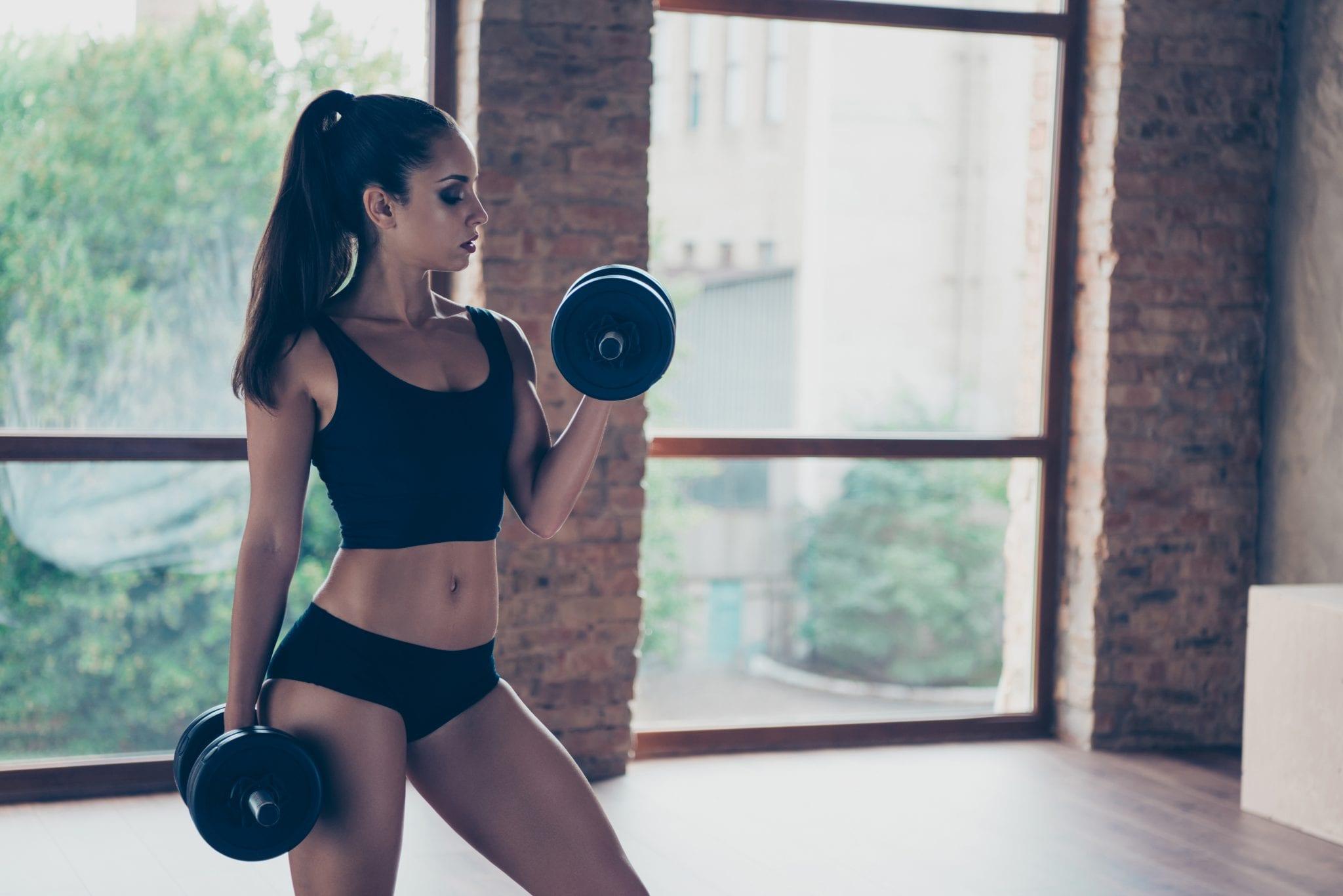 Fit attractive woman lifting dumbbells